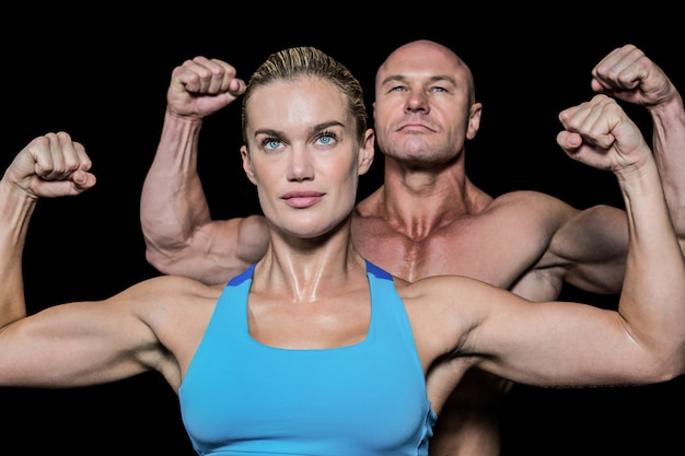Strong muscular man and woman flexing muscles against black background