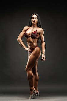 Strong and muscular sports girl in bikini posing