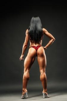 Strong and muscular sports girl in bikini posing