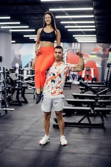 女性を肩に抱えてジムでポーズをとる強い筋肉のスポーツマン。ボディービル、健康的な生活
