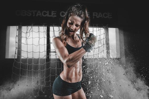 Сильная мускулистая женщина сгибает бицепс после тренировки.