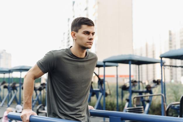 強い筋肉の若い男は、屋外のジムで運動しています