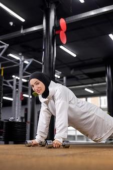 ジムで腕立て伏せのセットをしている強いイスラム教徒の女性、ダンベルを使用して、トレーニングに集中しているヒジャーブのスポーティーなアスリート女性