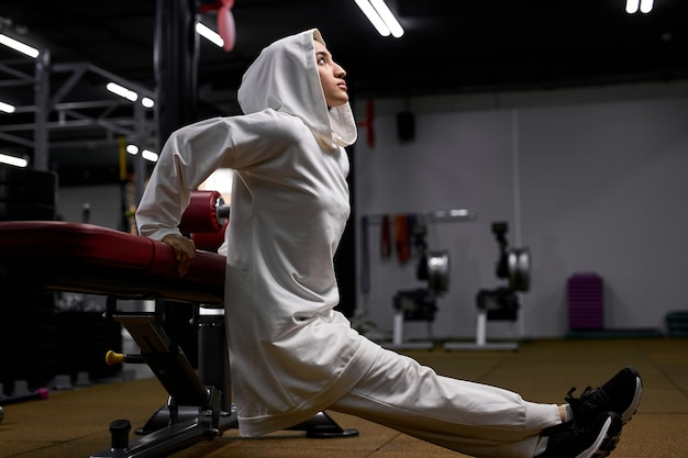 강렬한 훈련을받은 강한 이슬람 여성, 스포츠 장비에 몸을 기울이고 몸을 들어 올리고 쪼그리고 앉습니다. hijab에서 이슬람 여자 혼자 운동을