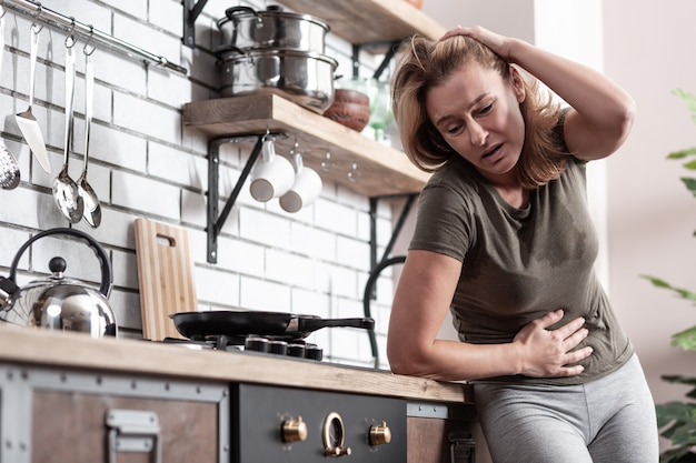 Strong pain. blonde-haired mature woman standing near cooker in kitchen suffering from pain