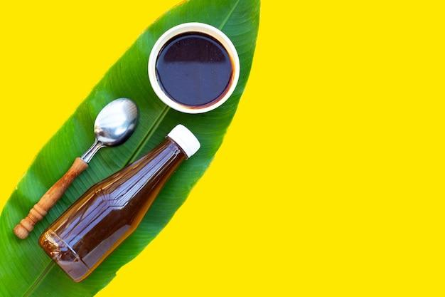 黄色の背景の緑の葉に強い魚醤のピクルス。