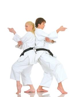 강력한 긍정적 인 젊은 쌍의 챔피언 karateka 매력적인 소녀와 기모노에서 용감한 젊은 남자가 서로 다시 서있는 포즈.