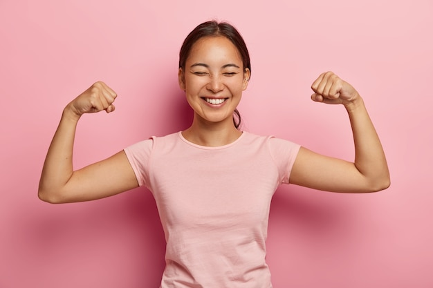 Strong powerful asian woman with dark combed hair, toothy smile, raises arms and shows biceps, has piercing in ear, wears casual rosy t shirt, models against pink wall. look at my muscles!