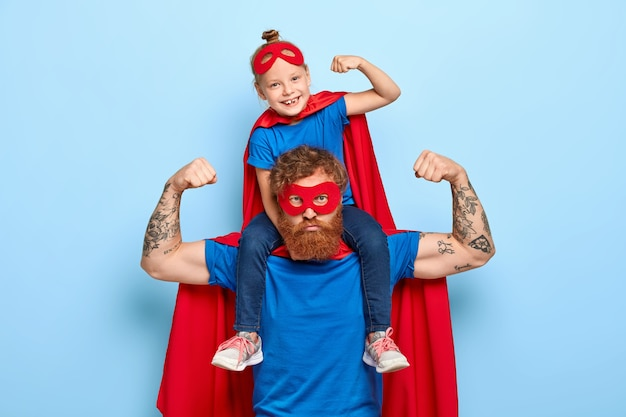 Strong powerful dad and little female child on his shoulders show muscles