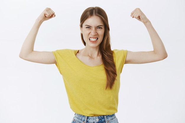 Strong and powerful girl flexing biceps, showing her strength