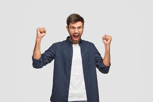 強くてパワフルな男が握りこぶしで手を上げ続け、驚きから大声で叫び、勝利を祝う