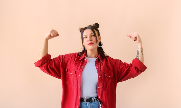 Strong powerful stylish woman with tattoo shows biceps feminism and women power