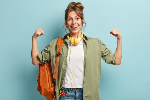 力強い女性が手を挙げて筋肉を見せ、表情が嬉しく、ヘッドホンをつけている