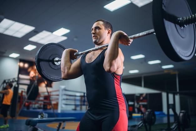 Сильный пауэрлифтер делает становую тягу со штангой в тренажерном зале