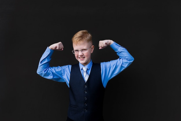 The strong schoolboy on a black background