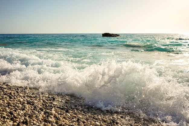 A strong sea wave on the beach hits a rocky shore on the island of lefkada, greece