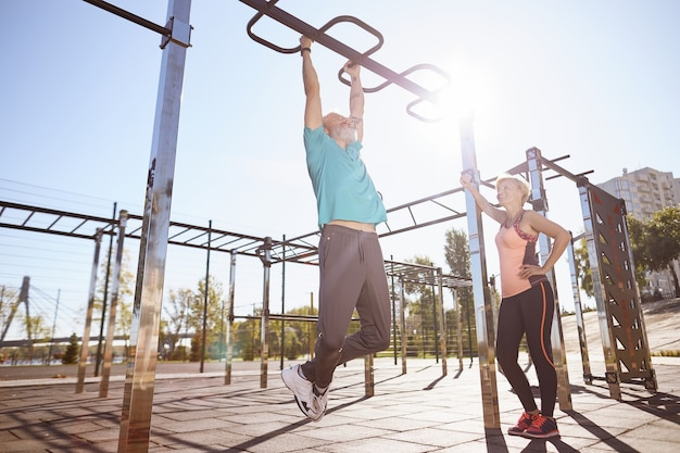妻と一緒にトレーニング中に鉄棒で懸垂をしているスポーツウェアの強い年配の男性