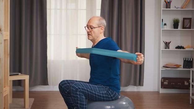 バランスボールとレジスタンスバンドを使用して居間で運動する強い年配の男性。老人年金受給者が自宅でヘルスケアスポーツを健康的に訓練し、高齢者でフィットネス活動を行う