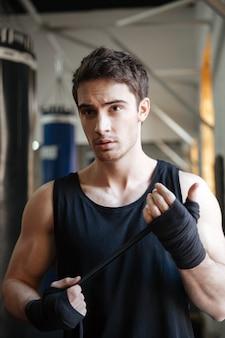 Сильный серьезный спортсмен, глядя во время тренировки