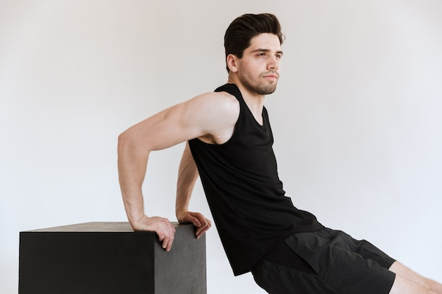 Strong serious young sports man isolated make exercises for triceps.