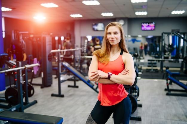 ジムの機器の近くでポーズをとるフィットネスの筋肉の体を持つ強いセクシーなブロンドの女性。スポーツの健康的な習慣の概念。上腕二頭筋を表示しています。