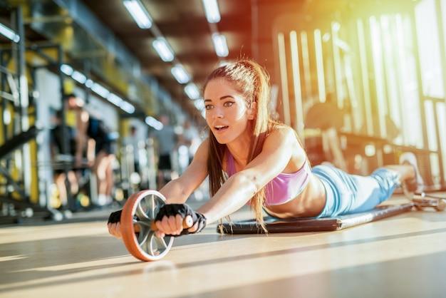 Сильная сексуальная молодая девушка, тренирующаяся в ярком тренажерном зале.