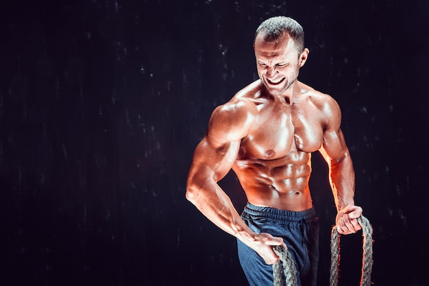Strong shirtless bodybuilder man working out hard with rope