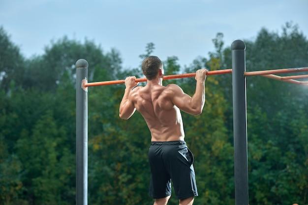 横棒のプルアップを行う強い上半身裸の男。