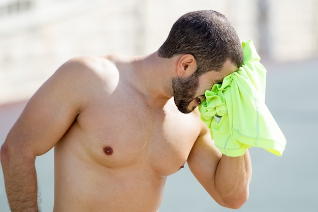 Strong shirtless man drying face with t-shirt