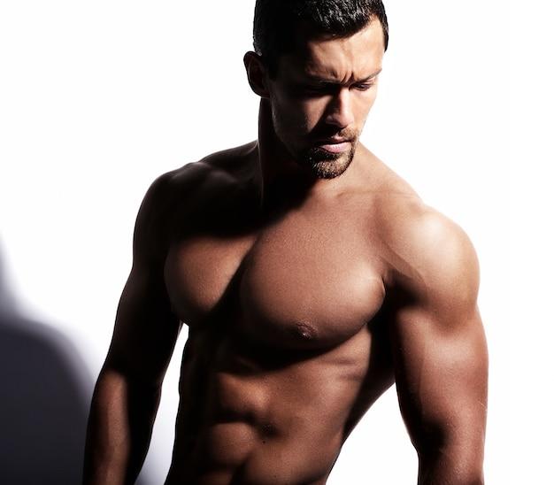 Strong shirtless man posing on white