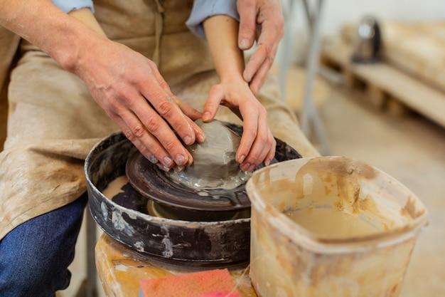 強い熟練したマスター。新しい土鍋を彫りながらろくろで一緒に働くロマンチックなカップル