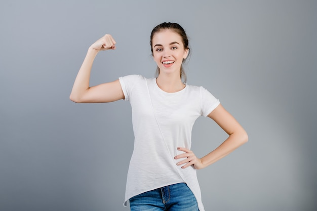 Strong slim fit brunette woman showing biceps isolated over grey