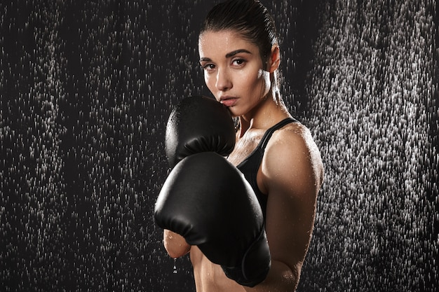 Strong slim woman boxing wearing gloves and standing in defense position under rain drops, isolated over black background