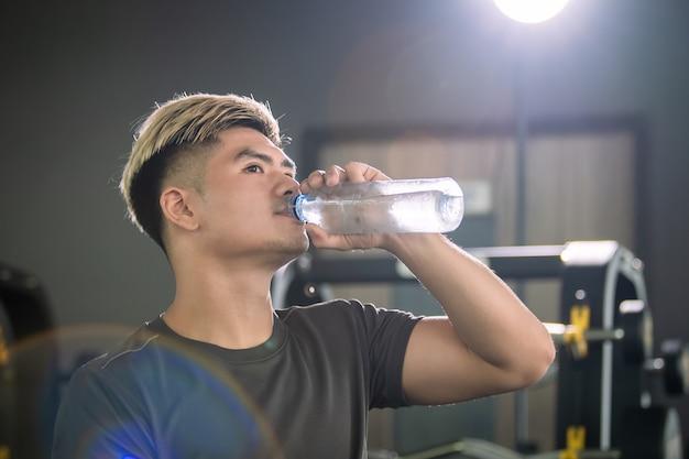 屋内ジムで運動した後、リラックスして水筒から水を飲む強いスポーツ男。若いアジアのアスリートは、冷たい水を飲むことによってトレーニングの後に自分自身をリフレッシュします。コピースペースのある画像。