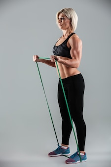 Strong sports woman exercising with resistance band, looking aside