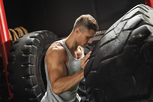 Сильный спортсмен делает упражнение с переворотом шин
