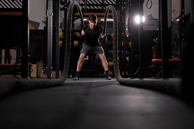 一人で激しいトレーニングをしながら、クロスフィットジムでバトルロープエクササイズをしている強いスポーツマン。スポーツウェアで、ジムで運動しながらクロスフィット運動をしている集中白人男性