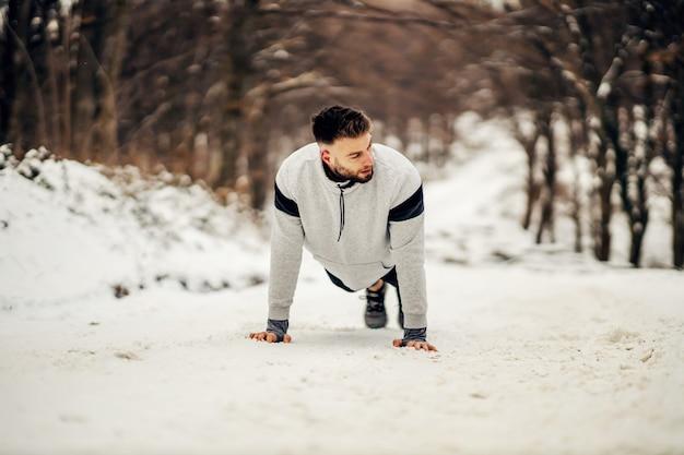 겨울에 눈 덮인 길에서 자연 속에서 팔 굽혀 펴기를 하는 강한 스포츠맨. 건강한 생활 방식, 겨울 피트니스, 근력 운동