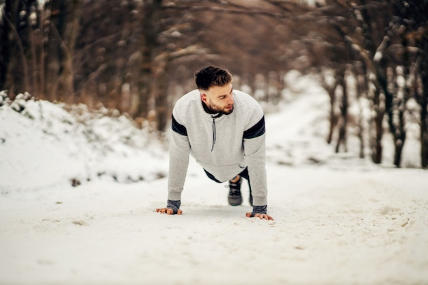 Strong sportsman doing push ups in nature on snowy path at winter. healthy lifestyle, winter fitness, strength exercises
