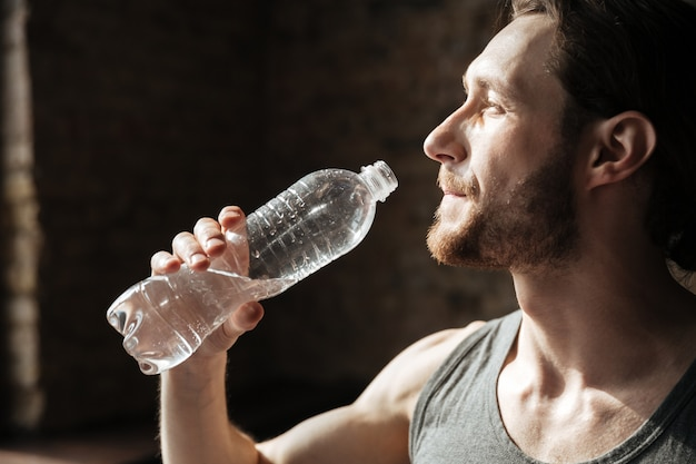 Strong sportsman in gym drinking water.