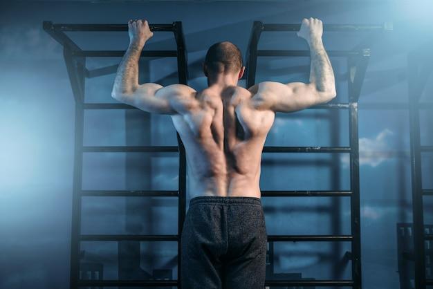 ジム、背面図の鉄棒でトレーニングする強力なスポーツマン。