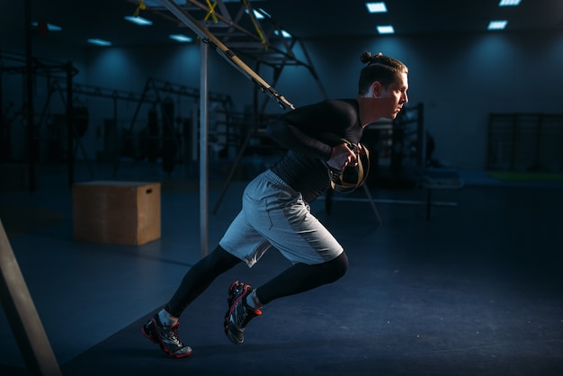 Strong sportsman on training, stretch endurance workout with ropes in gym.