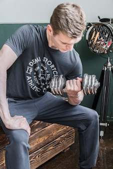 Strong sportsman training with dumbbell