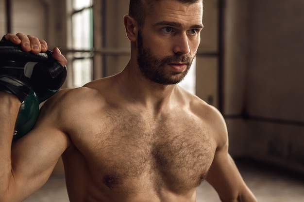 Strong sportsman with hairy chest exercising with kettlebell during fitness workout in gym