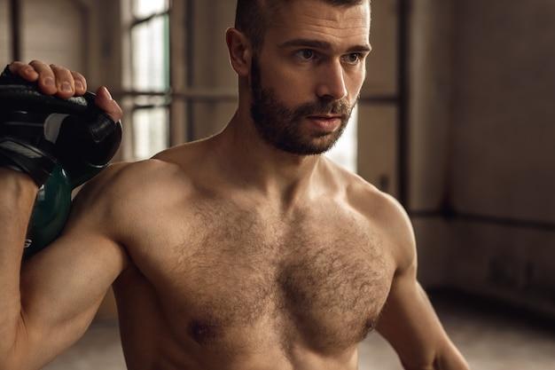 체육관에서 피트니스 운동을하는 동안 kettlebell로 운동하는 털이 많은 가슴을 가진 강한 운동가