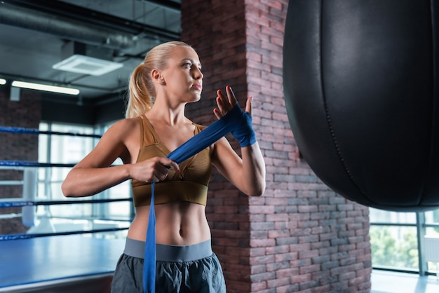 Strong sportswoman. appealing strong sportswoman wearing stylish comfortable clothes working out in gym