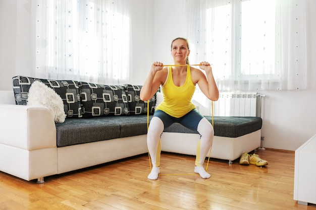 Strong sportswoman doing fitness exercises with power rubber at home during lockdown.