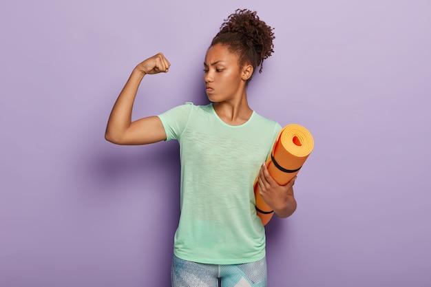 Сильная спортсменка занимается фитнесом в помещении, показывает мышцы после тренировки