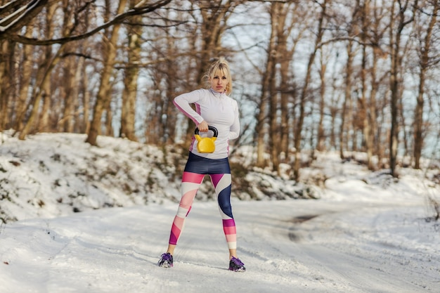 雪の降る冬の日に自然の中で立っている間ケトルベルを持ち上げる強いスポーツウーマン。ボディービル、健康的な生活、アウトドアフィットネス