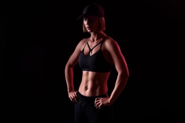 筋肉質の腹部を持つスポーツブラを身に着けている強いスポーツウーマンは、黒い背景の上にヘッドフォンで音楽を聴きます。完璧な体型
